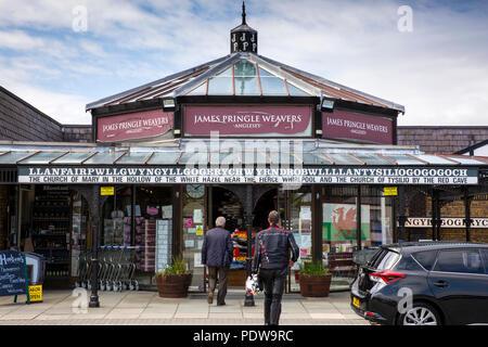 UK, Wales, Anglesey, Llanfairpwllgwyngyllgogerychwyrndrobwllllantysiliogogogoch James Pringle Weavers shops with village name sign and translation - Stock Image