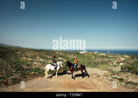 Couple with horses riders enjoy the landscape on the top of a mountain with ocean and horizon view - alternative vacation lifestyle in the nature - Stock Image