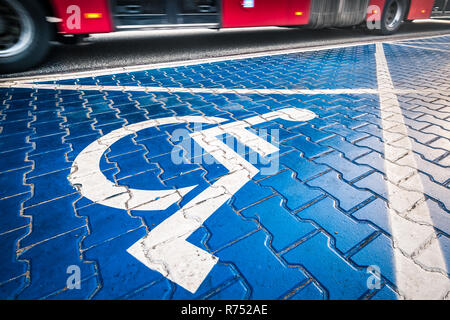 handicapped blue parking place sign in Warsaw, Poland, red blurred bus in the background - Stock Image