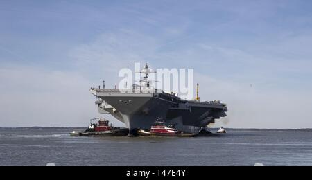 NEWPORT NEWS, Va. (March 17, 2019) USS Gerald R. Ford (CVN 78) is maneuvered by tugboats in the James River during Ford's turn ship evolution. Ford is currently undergoing its post-shakedown availability at Huntington Ingalls Industries-Newport News Shipbuilding. - Stock Image