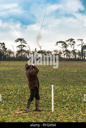 A man who has just fired a shotgun and the column of shot can be seen leaving the end of the barrel - Stock Image