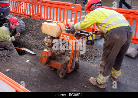 Workmen using a mini excavator and powered saw to make a trench in the road for an electrical power cable - Stock Image
