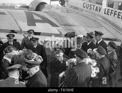 The crew of a Junkers Ju 52 is greeted after a North Atlantic crossing at the Berlin Tempelhof Airport. - Stock Image