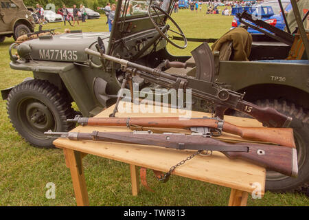 Collection of British and German weapons on show alongside American Jeep. - Stock Image