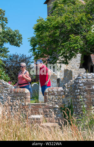 Walkers on the public footpath  using the  Stone steps stile to cross over on the flint  stone wall at st peter and paul church west wittering - Stock Image