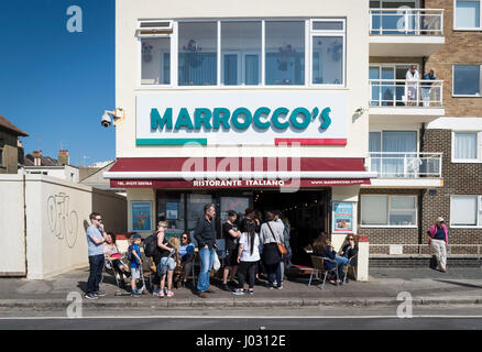 People in a queue outside the famous Marrocco's Italian restaurant and gelato ice cream shop on the seafront - Stock Image