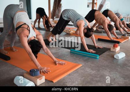 Multiple people exercising yoga on mats - Stock Image