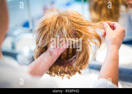 Woman holding wig. - Stock Image