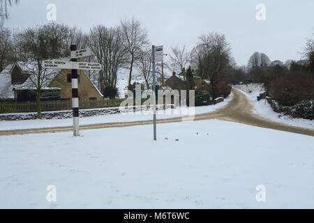 Bus stop and directional road sign after a March snowfall, Hook Norton, Oxfordshire - Stock Image