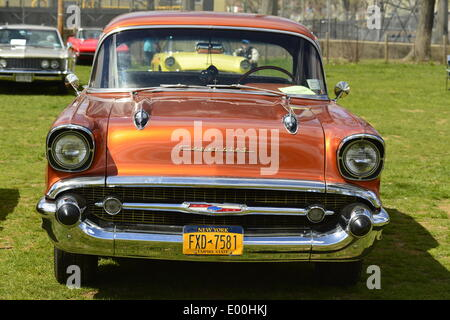 Floral Park, New York, U.S. 27th April, 2014. An orange 1957 Chevrolet Bel Air, with chrome front grille and hood ornaments, is exhibited by members of the New York Antique Auto Club at the 35th Annual Antique Auto Show at Queens Farm. Credit:  Ann E Parry/Alamy Live News - Stock Image