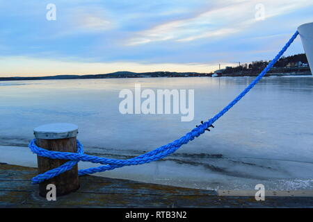 Close up of a blue rope mooring a ship in an ice covered harbor bay. - Stock Image