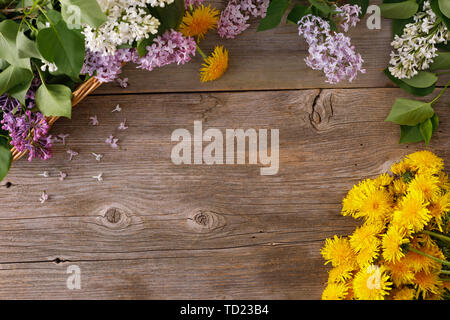 Decor of flowers on the background of vintage wooden planks.Vintage background with lilac flowers and dandelion and place under the text. View from ab - Stock Image