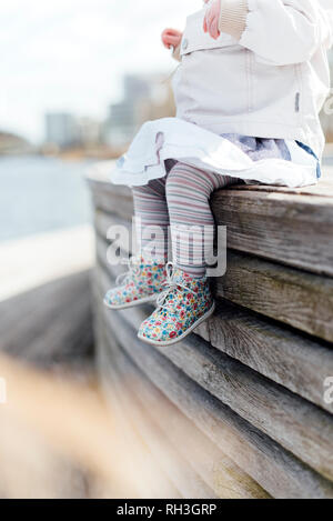 Girl sitting, low section - Stock Image