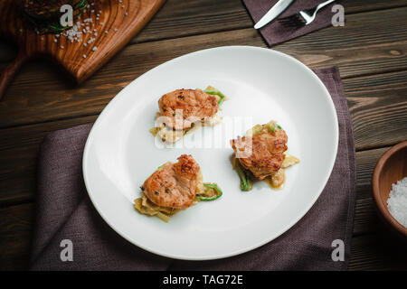 Chicken medallions on a pillow of vegetables. Cafe menu on a wooden background in warm colors with copy space. - Stock Image