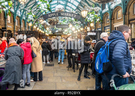 Apple Market, part of Covent Garden, bustling with shoppers and vistitors. Christmas decorations of giant suspended mistletoe and silver baubles. - Stock Image
