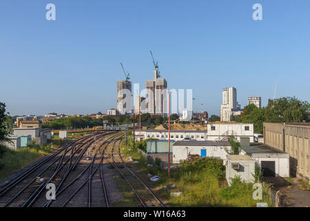 The changing skyine of Woking, Surrey: railway tracks lead into tower cranes and new high rise mixed use developments in the town centre - Stock Image