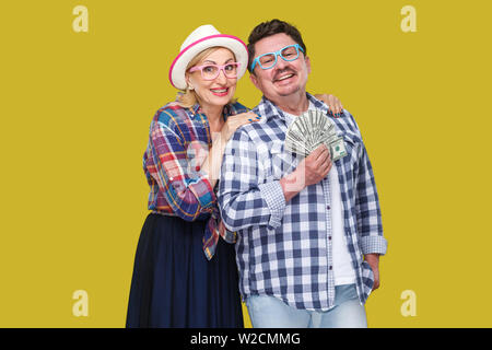 Happy wealthy family, adult man and woman in casual checkered shirt standing pickaback together, holding fan of dollar, toothy smile, looking at camer - Stock Image