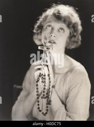 Woman praying with rosary beads - Stock Image