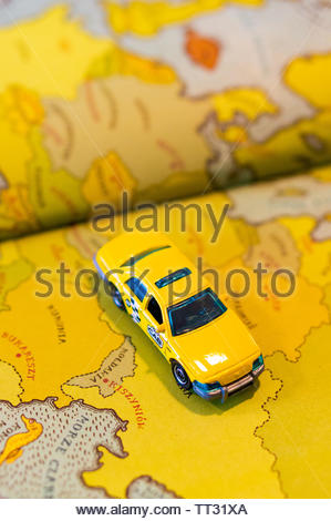 Mattel Matchbox yellow toy Ford Crown Victoria taxi car on a map from a opened book on circa June 2019 in Poznan, Poland. - Stock Image