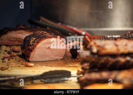 Canadian bacon, also known as peameal, for sale, grilled and cooked, being ready to be cut on a wooden plank, surrounded by other cooked meats.  Pictu - Stock Image