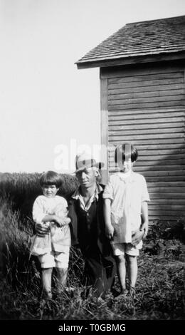 Dad stands with his two daughters for a portrait outside the house, ca. 1935. - Stock Image