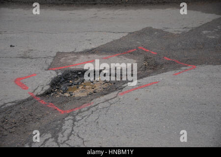 Roadside pothole on the edge of the road in the north Oxfordshire village of Hook Norton - Stock Image