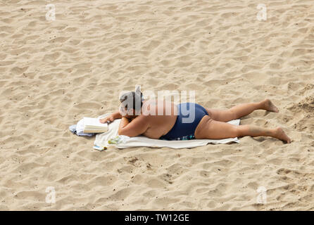 Obese, overweight woman reading book on beach in Spain. - Stock Image