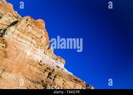 Red and orange rocks form a cliff face above the hot sands of the desert floor. - Stock Image