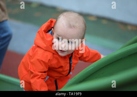 Beautiful Baby Boy With Orange Raincoat Climbing Up The Slide, Close Up Portrait View - Stock Image