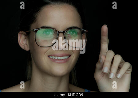 Young woman smiling with finger raised, portrait - Stock Image