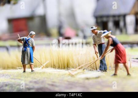 Miniature model of farmers harvesting wheat, at Kolejkowo, Wrocław, Wroclaw, Wroklaw, Poland - Stock Image