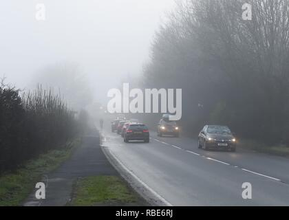 A cyclist with no lights almost disappearing in fog on a busy road near Glasgow in Scotland, UK, Europe. - Stock Image