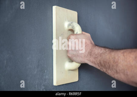 Workers hand with a trowel smoothing a wall with decorative plaster - Stock Image