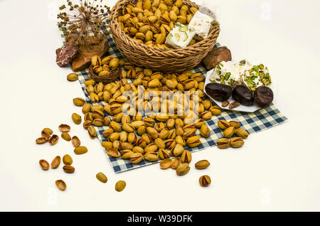 Scattered from a wicker basket pile of pistachios with persimmons and nougat on a white plate with stones and dry twigs on paper covered with blue squ - Stock Image
