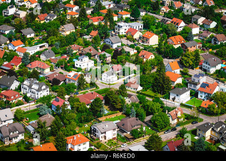 Suburban neighborhood with modern living residential houses. Ecologically clean places for living. Solar batteries on the roofs. Suburban infrastructu - Stock Image