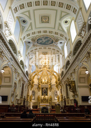 Quebec City's Notre-Dame Cathedral interior: Interior of la Basilica Cathedrale Notre-Dame de Quebec front/altar view. Two worshipers are in the pews and one tourist looks around. - Stock Image