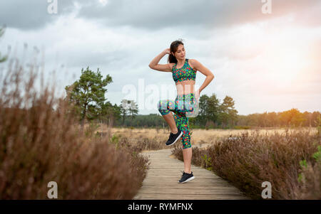 woman doing exercises in the morning sun - Stock Image