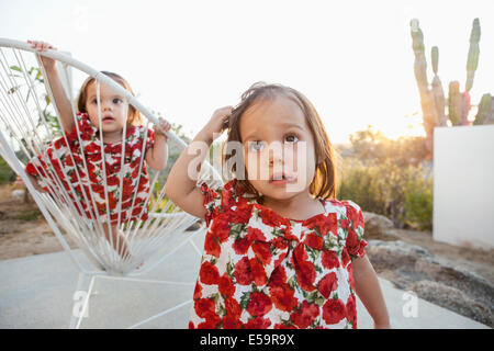 Twin baby girls playing on patio - Stock Image