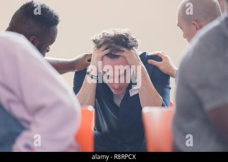 Men comforting upset man in group therapy - Stock Image