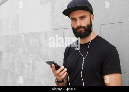 Bearded Muscular Man Wearing Black Tshirt Blank Snapback Cap Summer Time.Young Men Smiling Opposite Empty Gray Concrete - Stock Image