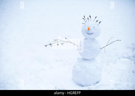 Smiling snowman standing in the snow - Stock Image