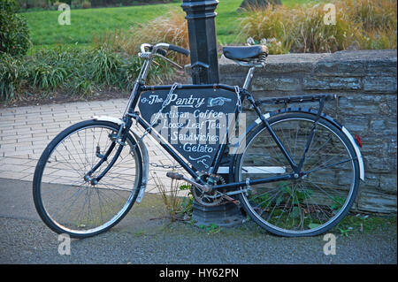An old black bicycle chained to a lamp post and leaning against a stone wall. - Stock Image