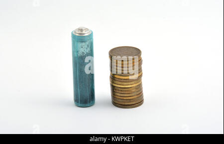 Three AAA batteries with coins isolated on white background - Stock Image