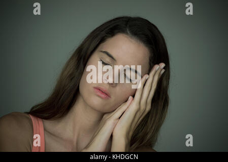 Young woman resting head on hands with eyes closed - Stock Image