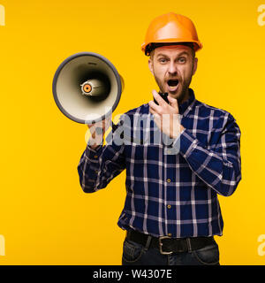 Angry worker man in orange helmet with a megaphone on yellow background - Image - Stock Image