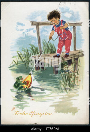 A greeting postcard printed in Germany, shows the boy launching a boat in the water. Inscription in German: Happy - Stock Image