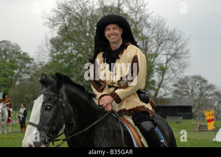 Squire in gold on horseback - Stock Image