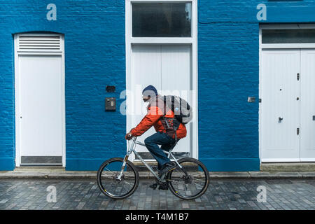 A man on a bicycle cycling past a house painted blue and white. - Stock Image