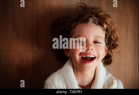 A close-up portrait of happy small girl with white knitted sweater lying on the floor, a top view. - Stock Image