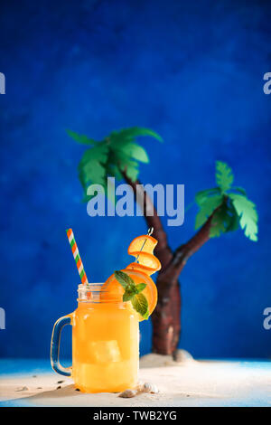 Decorated tropical cocktail in a glass jar on a blue background with copy space. Papercraft palm trees with yellow juice. - Stock Image